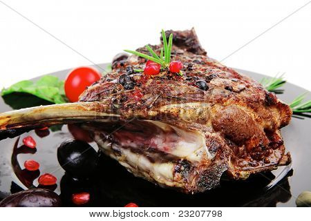 grilled ribs rack over black plate with cutlery