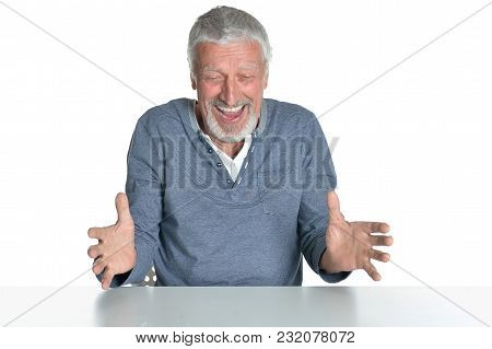 Portrait Of   Senior Man Sitting At Table  Isolated On White Background