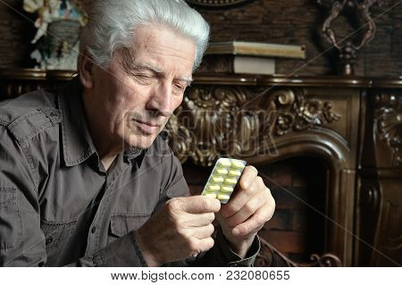 Portrait Of Sick Senior Man With Pills Posing At Home