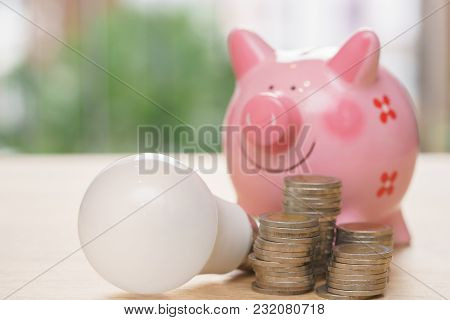 Piggy Bank With Light Bulb And Stack Coins On Wooden Desk - Save Energy Concept.