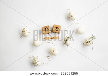 Easter white eggs are minimalistically decorated with twine and gypsophila. With a wooden calendar.