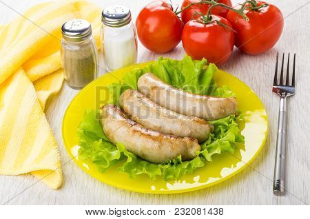 Fried Chicken Sausages On Leaves Of Lettuce In Plate, Napkin, Bunch Of Tomatoes, Pepper, Salt And Fo