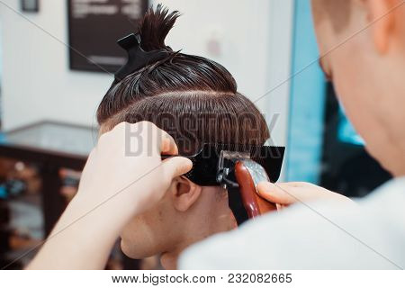Men's Hairstyling And Haircutting With Hair Clipper In A Barber Shop Or Hair Salon. Bearded Brutal M