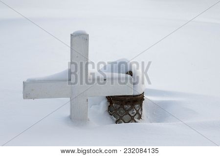 Graveyard In Winter, A Small Wooden Cross And A Lantern Covered In Snow. Norway