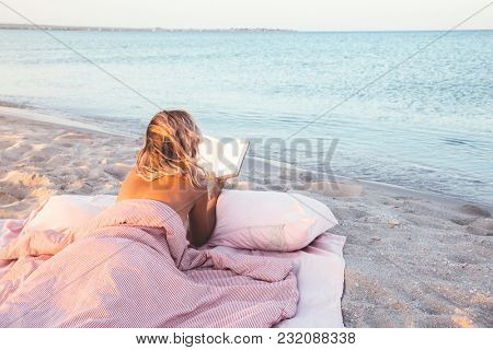 Relax concept. Cozy and comfortable bed near the sea. Summer vacations still life. Woman reading a book.