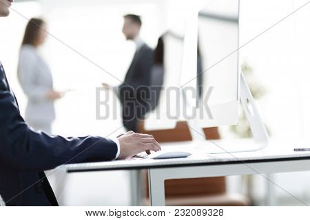 employee is typing on the computer keyboard.