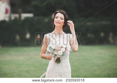 Beautiful Brunette Bride In Elegant White Dress Holding Bouquet Posing Neat Trees.