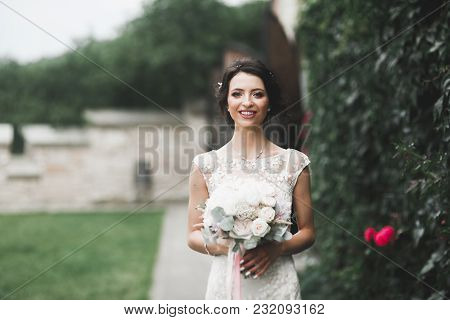 Beautiful Bride In Elegant White Dress Holding Bouquet Posing In Park.