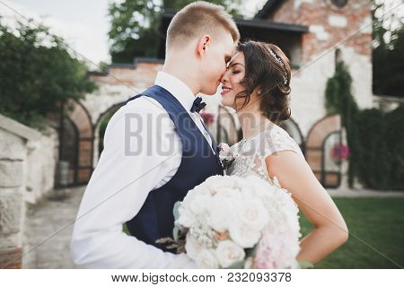 Romantic, Fairytale, Happy Newlywed Couple Hugging And Kissing In A Park, Trees In Background.