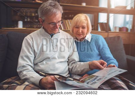 Beautiful Old Couple Are Sitting On The Couch Together And Reading A Big Newspaper. Man Is Using Rea