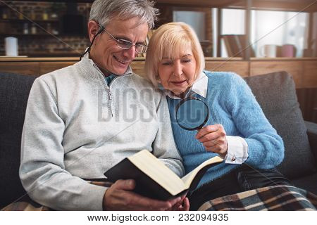 Close Up Of Old Couple Reading A Book. He Is Using Glasses For Reading While She Is Holding A Loop A