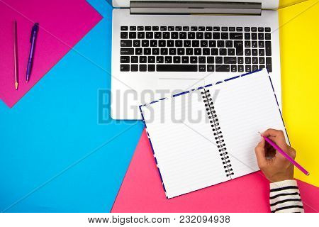 Woman Hands Writing And Using Laptop On Colorful Background.
