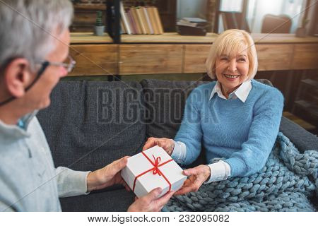 Cut View Of Nice And Cute Grandparents. He Is Giving A Gift To His Wife. She Is Receiving That With