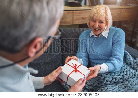 Close Up And Cut View Of Old Man Giving A Gift To Hai Wife. He Like To Do That. The Woman Looks Surp