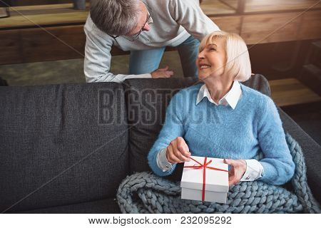 Beautiful Couple Is In A Room. He Is Standing Besides His Wife. She Has Recently Got A Present For H