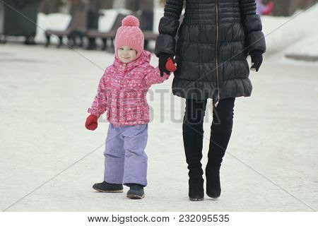 Little Cute Girl Walking In The Snow And Falling Into The Snowbank For A Walk With Her Mom, Winter F
