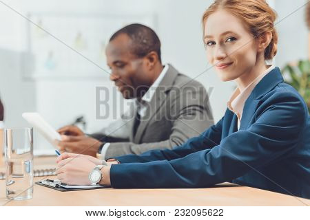 Woman In Formal Suit Looking At Camera At Office Space