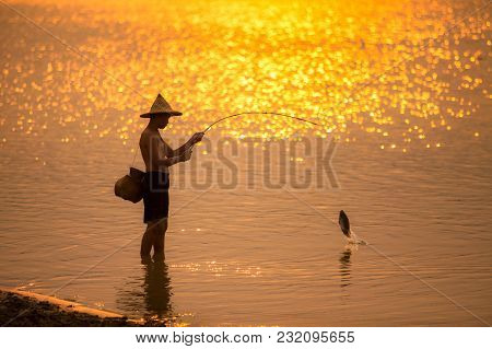 Asian Boy Fishing At The River Near Sunset