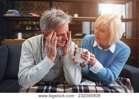 Another Picture Of Senior Couple. Close Up. Man Has A Headache. His Wife Is Suggesting Him To Drink