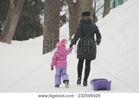 Little Cute Girl Walking In The Snow And Falling Into The Snowbank For A Walk With Her Mom, Rear Vie