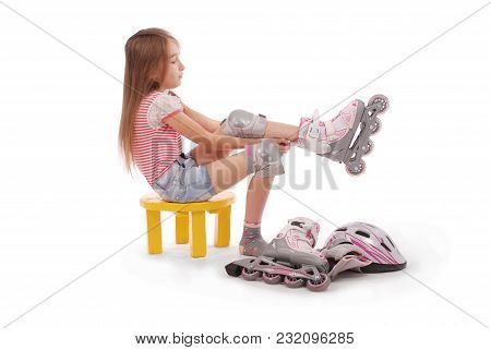 Charming Broun-haired Girl Of School Age In Short Jeans Shorts And A Pink T-shirt Sitting On The Cha