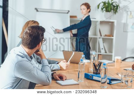 Businesspeople Sitting At Table And Looking To Woman Pointing On Flipchart At Office Space
