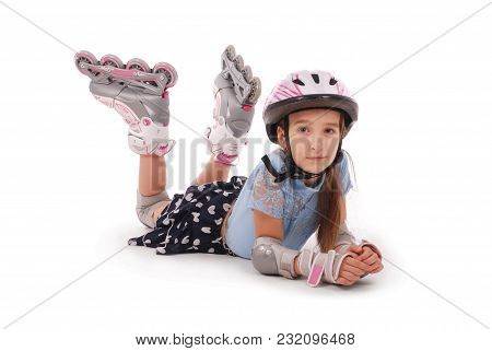 Happy Little Girl With Roller Skates And Protective Gear Lying On The  Floor - Isolated On White Bac