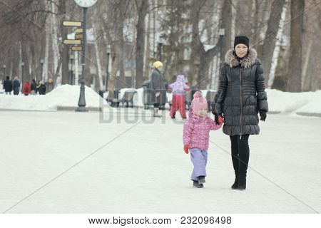 Little Cute Girl Walking In The Snow For A Walk With Her Mom, Winter Family Entertainment Concept