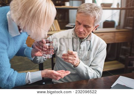 Close Up And Cut View Of A Man Getting A Few Pills And A Glass Of Water To Use The Medicine