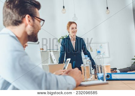 Businesswoman In Formal Suit Standing Against Table And Speaking To Team At Office Space
