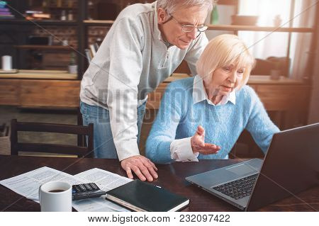 Woman Is Sitting At The Table And Trying To Understand How Ths Laptop Works. Her Husband Is Helping