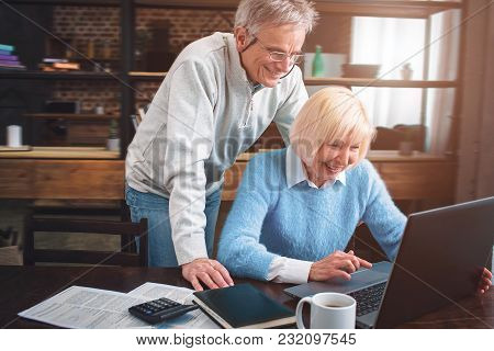 Man And Woman Are Looking To The Laptop's Screen And Laughing. T