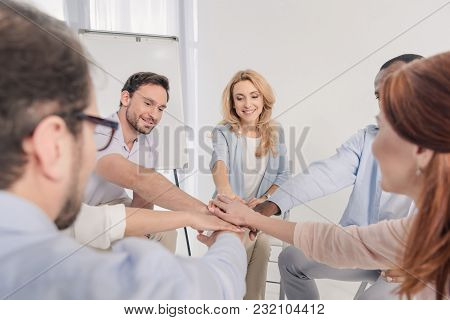 Selective Focus Of Middle Aged Multiethnic People Stacking Hands During Group Therapy