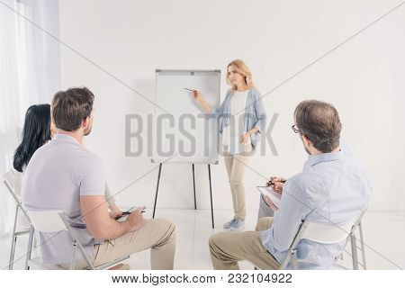 Middle Aged Woman Pointing At Blank Whiteboard During Anonymous Group Therapy