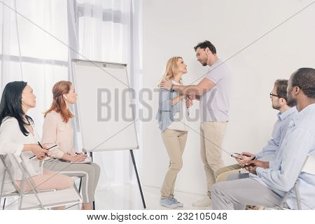 Mature Couple Looking At Each Other While Standing Near Blank Whiteboard And Other People Sitting On