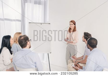Middle Aged Woman Standing Near Blank Whiteboard And Looking At Multiethnic People During Group Ther