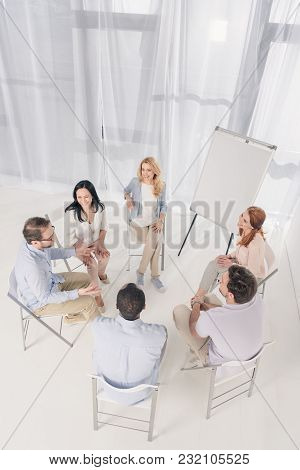 High Angle View Of Middle Aged People Sitting On Chairs And Talking During Group Therapy
