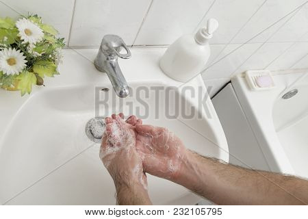 Close Up Of A Man Washing Hands, Using Liquid Soap. Selective Focus On The Hand