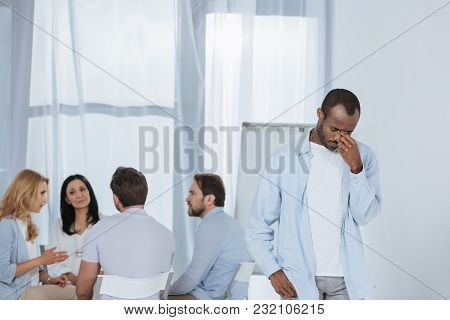 Middle Aged African American Praying While People Sitting Behind During Group Therapy