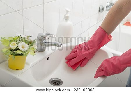 Close Up Of Female Hands Wearing Protective Gloves, Cleaning Bathroom Sink With Sponge