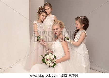 The Female Bride And Little Pretty Girls With Flowers Dressed In Wedding Dresses. Lovely Little Girl
