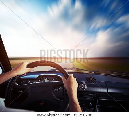 Driver's hands on a steering wheel and motion blurred road and sky