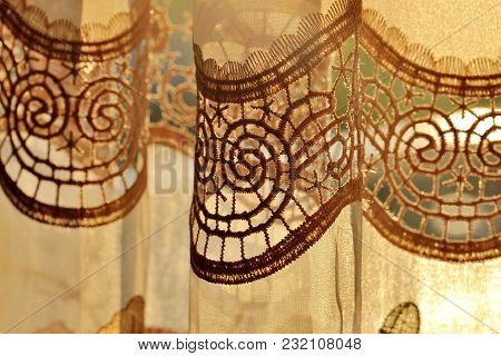 Close-up Detail Of Luxury Draped Golden Decorative Curtain With Flowers Ornamental Indoors At Sunset