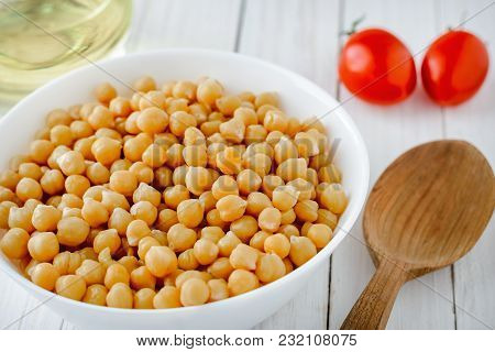 Cooked Chickpeas With A Plate, Tomatoes And Olive Oil On A Wooden Table. Tasty, Healthy Vegetarian F