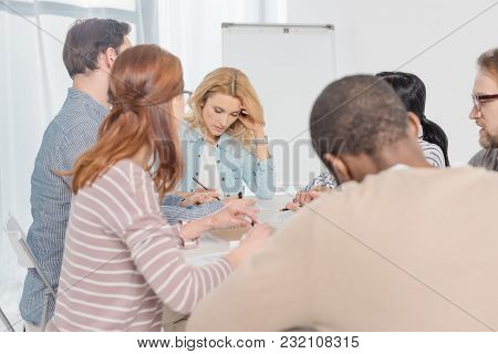 Multiethnic People Gathered Together And Taking Notes During Group Therapy