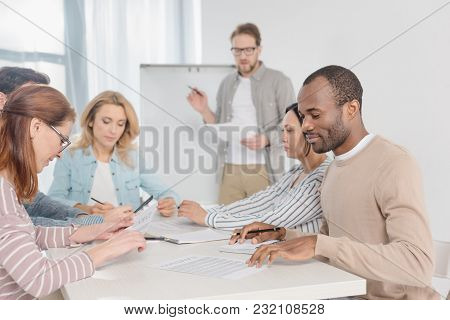 Multiethnic Team Working With Papers Together While Man Standing Near Whiteboard Behind