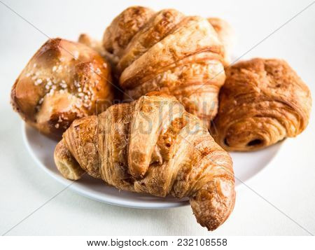 Closeup View Of A Variety Of French Croissants And Buns On A White Plate And Table