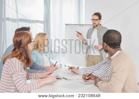 Middle Aged Man In In Eyeglasses With Papers Standing At Whiteboard And Having Conversation With His