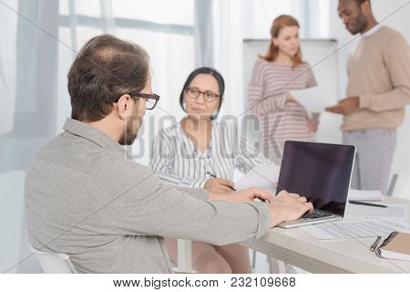Mature Man Using Laptop With Blank Screen While Multiethnic People Sitting And Standing Behind