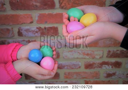 Children Holding Easter Eggs. A Boy And A Girl Each Hold Three Pastel Colored Easter Eggs Against A